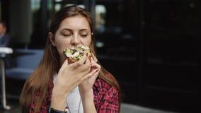 Mujer joven preciosa que come el bocadillo delicioso fresco en café de la calle de la ciudad almacen de video