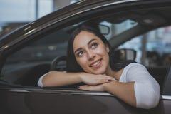 Mujer joven preciosa que compra el nuevo coche en la representación imagen de archivo