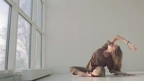 Mujer joven preciosa que dobla al lado mientras que practica yoga almacen de metraje de vídeo