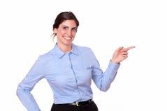 Mujer joven preciosa que señala a su izquierda Fotos de archivo