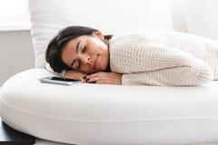 Mujer joven preciosa que se relaja en un sof? en casa foto de archivo libre de regalías