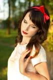 Mujer joven, presentando dulce en el jardín Fotos de archivo