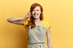 Mujer joven presionada, infeliz, enojada, frustrada que habla en el teléfono imagen de archivo