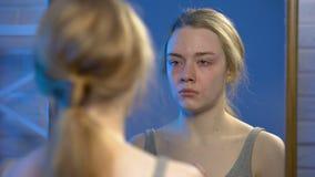 Mujer joven presionada que llora mirando la reflexión de espejo, problemas de la desesperación almacen de metraje de vídeo