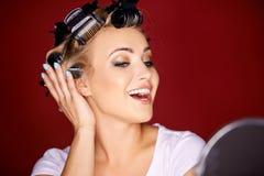 Mujer joven primping delante de un espejo Imágenes de archivo libres de regalías