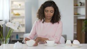 Mujer joven que añade demasiado azúcar en la taza de té, forma de vida malsana, diabetes almacen de metraje de vídeo