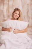 Mujer joven que abraza la almohada Fotos de archivo
