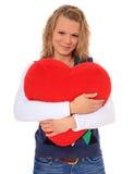 Mujer joven que abraza la almohadilla en forma de corazón Fotografía de archivo libre de regalías