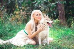 Mujer joven que abraza su perro esquimal del perro en el bosque Imagenes de archivo