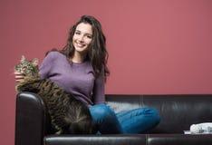 Mujer joven que abraza un gato Imágenes de archivo libres de regalías