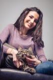 Mujer joven que abraza un gato Imagenes de archivo