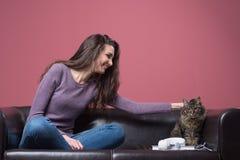 Mujer joven que abraza un gato Fotos de archivo