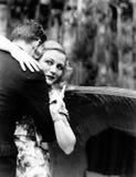Mujer joven que abraza a un hombre y que señala hacia un tablero de la información (todas las personas representadas no son vivas imagen de archivo libre de regalías