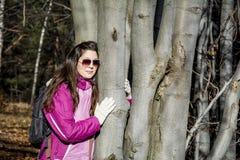 Mujer joven que abraza un tronco del roble en el bosque Imagen de archivo libre de regalías