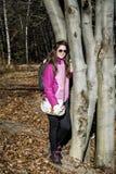 Mujer joven que abraza un tronco del roble en el bosque Imagenes de archivo