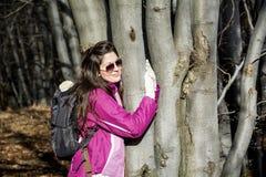 Mujer joven que abraza un tronco del roble en el bosque Foto de archivo libre de regalías