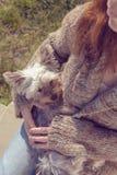 Mujer joven que abraza y que abraza su perro de perrito del terrier de Yorkshire en su revestimiento Imagen de archivo