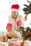 Mujer joven que abre un presente el mañana de la Navidad Fotos de archivo libres de regalías