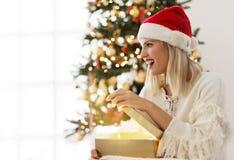 Mujer joven que abre un presente el mañana de la Navidad Fotografía de archivo libre de regalías