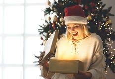 Mujer joven que abre un presente el mañana de la Navidad Foto de archivo libre de regalías