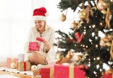 Mujer joven que abre un presente en una mañana de la Navidad hermosa Fotografía de archivo
