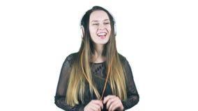 Mujer joven que acanala mientras que escucha la música en sus auriculares y hace caras divertidas almacen de metraje de vídeo