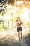 Mujer joven que activa en el camino rural en naturaleza del bosque Imagen de archivo