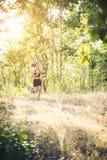 Mujer joven que activa en el camino rural en naturaleza del bosque Foto de archivo