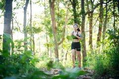 Mujer joven que activa en el camino rural en naturaleza verde del bosque Imagenes de archivo
