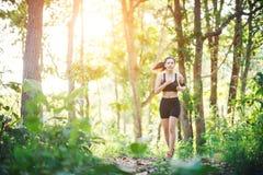 Mujer joven que activa en el camino rural en naturaleza verde del bosque Foto de archivo