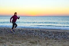 Mujer joven que activa en la orilla del mar que hace aptitud de la mañana fotografía de archivo libre de regalías
