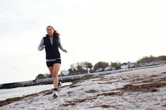 Mujer joven que activa a lo largo de la playa Fotos de archivo