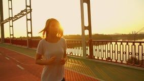 Mujer joven que activa a lo largo del puente almacen de metraje de vídeo