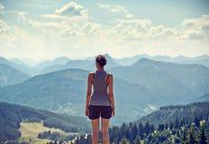 Mujer joven que admira una opinión de la cima de la montaña fotografía de archivo