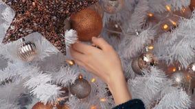 Mujer joven que adorna el árbol de navidad con las chucherías Preparación del Año Nuevo, cierre para arriba almacen de metraje de vídeo