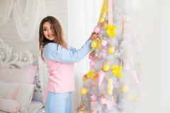 Mujer joven que adorna el árbol del Año Nuevo Imagen de archivo libre de regalías