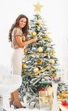 Mujer joven que adorna el árbol de navidad con la bola de la Navidad Imagenes de archivo