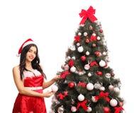 Mujer joven que adorna un árbol de navidad Foto de archivo