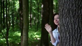 Mujer joven que agita de detrás árbol en el bosque almacen de video