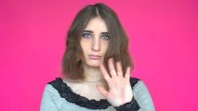 Mujer joven que agita un saludo Presentación contra un fondo rosado desprendible metrajes