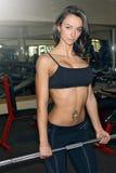 Mujer joven que agujerea un barbell en una posición del deadlift en el gimnasio Imagen de archivo