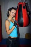 Mujer joven que agujerea una bola de sacador en el gimnasio Imagen de archivo