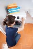 Mujer joven que ajusta el dial en la lavadora Fotos de archivo libres de regalías