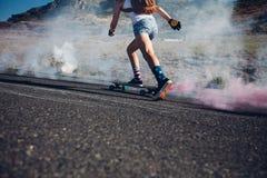 Mujer joven que anda en monopatín en un camino Foto de archivo