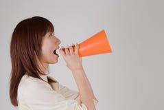 Mujer joven que anima con el megáfono Imagen de archivo libre de regalías