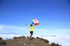 Mujer joven que anima funcionada con con los globos coloridos fotos de archivo