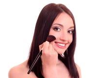 mujer joven que aplica blusher Foto de archivo