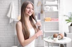 Mujer joven que aplica el aceite sobre el pelo fotografía de archivo