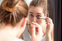 Mujer joven que aplica el rimel en sus pestañas más bajas con el espejo Fotografía de archivo