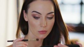 Mujer joven que aplica el sombreador de ojos metrajes